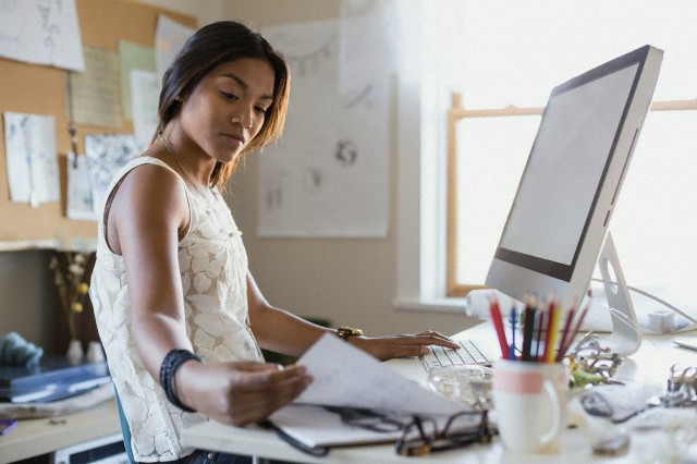 Female jewelry artist with sketch book working on computer in home office
