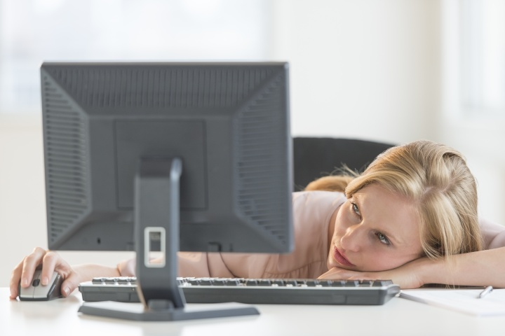 Businesswoman Looking At Desktop PC While Leaning On Desk